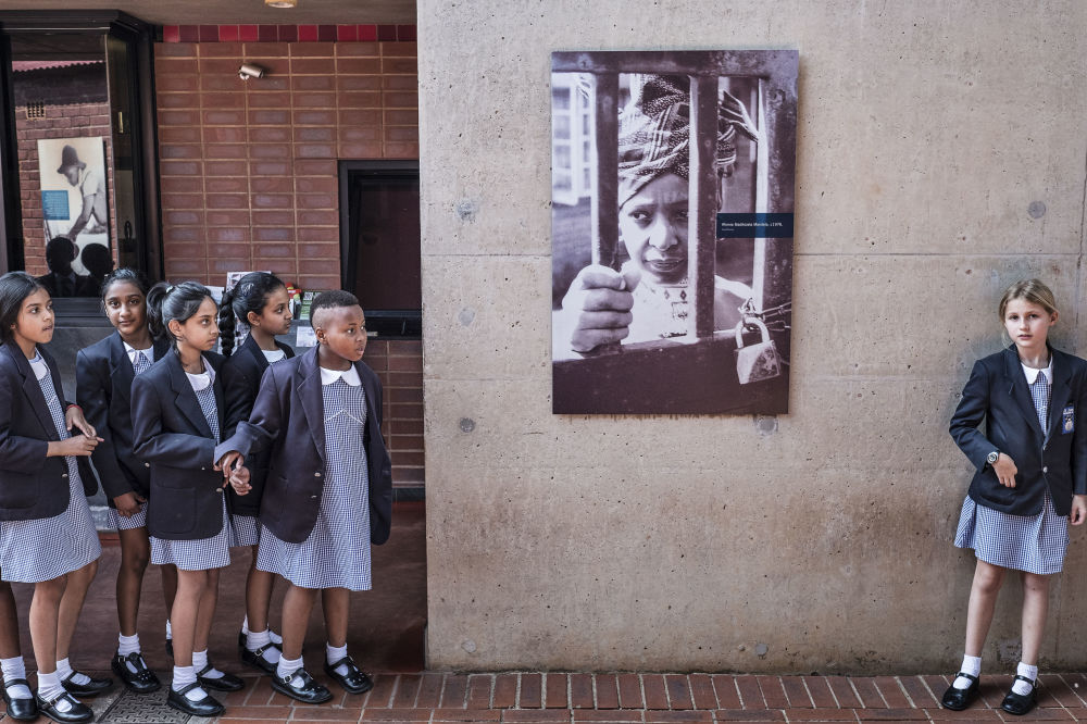 أطفال المدارس في جنوب أفريقيا يتوفون أمام صورة للناشطة المناهضة لنظام الفصل العنصري في جنوب أفريقيا ويني ماديكيزيلا - مانديلا، الزوجة السابقة لزعيم المؤتمر الوطني الأفريقي نيلسون مانديلا، على جدار منزلها في سويتو 3 أبريل/ نيسان  2018