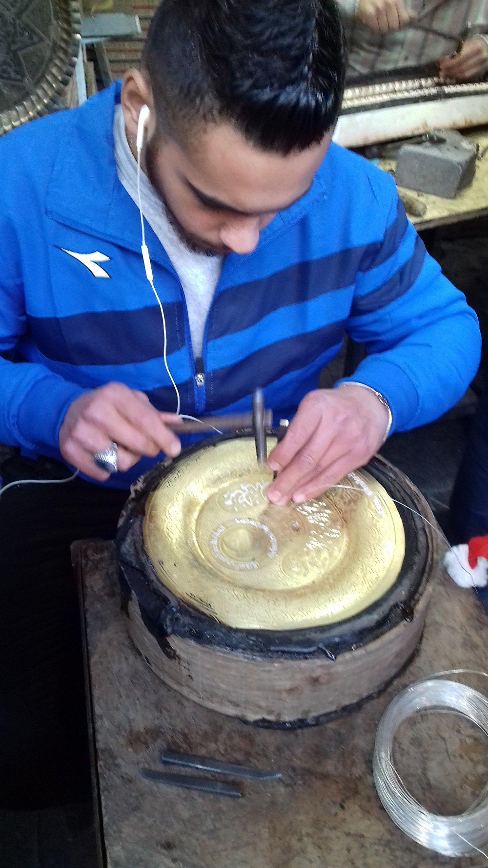 حرفي دمشقي يقوم بممارسة مهنته في تطعيم النحاس