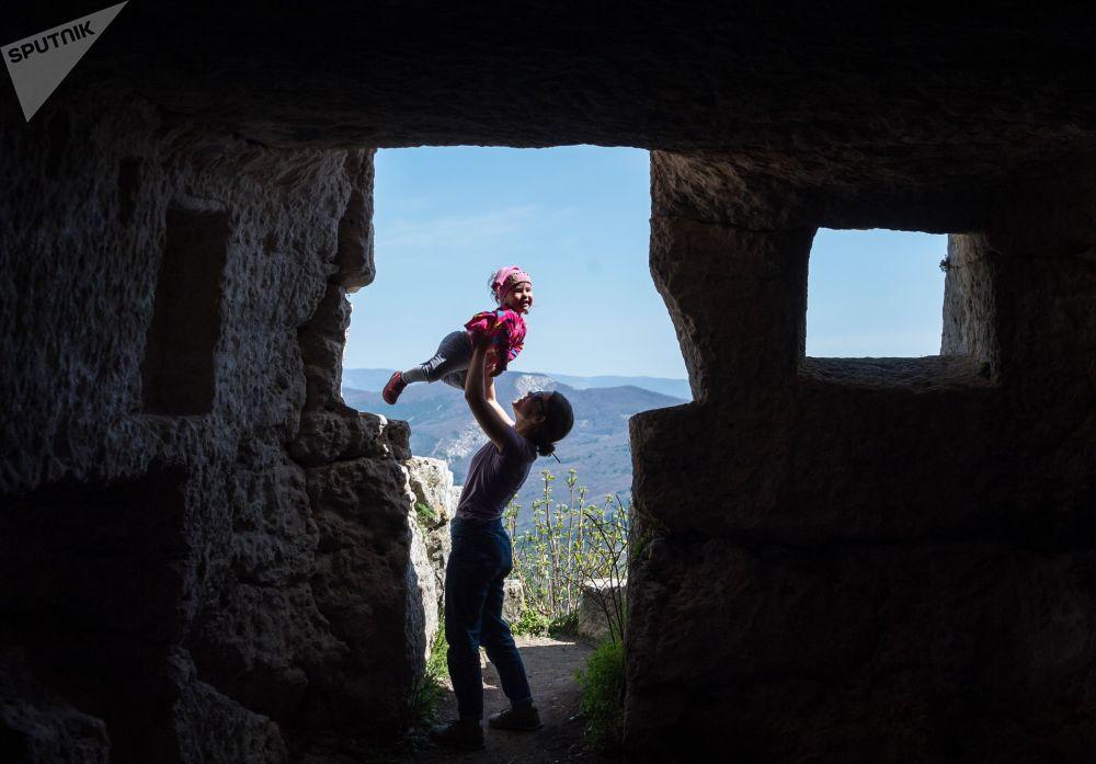 فتاة تمسك طفلة في منطقة ذات كهوف مانغوب في منطقة باختشيسارايسك في القرم/ روسيا