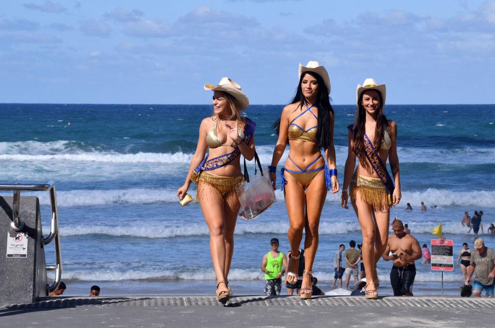 فتيات حارسات يتفقدن موقف السيارات المدفوع، قبالة شاطئ سرفرز بارادايس (Surfers Paradise)  في مدينة جولد كوست الأسترالية خلال دورة ألعاب جود ويل.