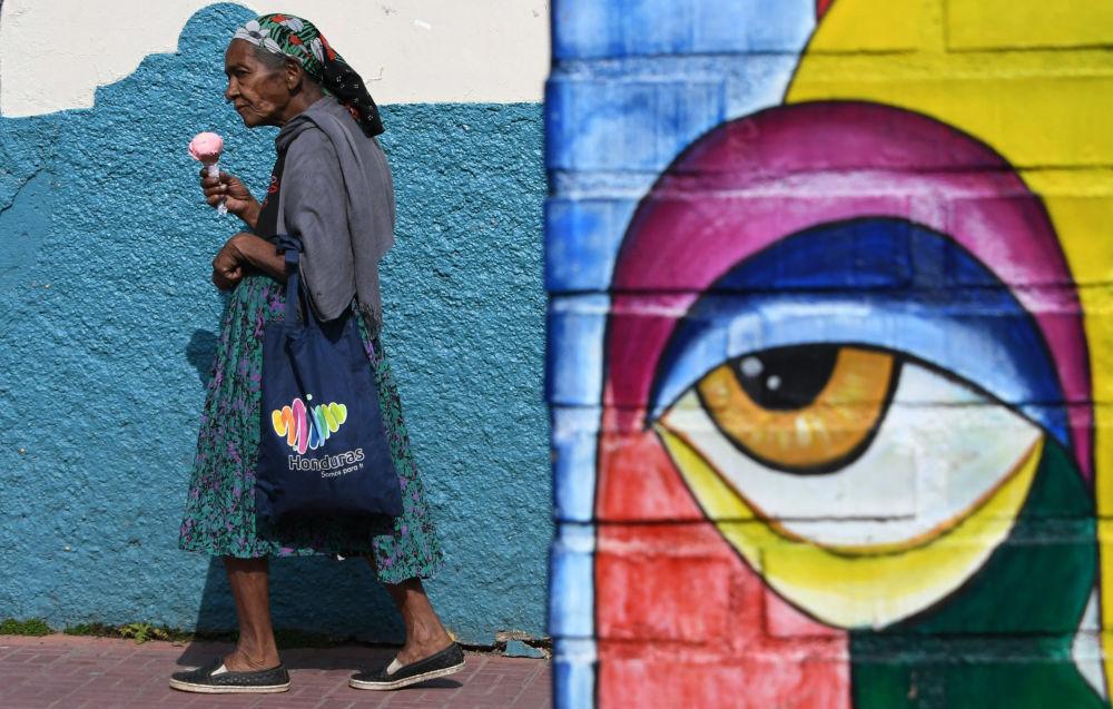 امرأة تسير حاملة مثلجات على خلفية جدارية في شارع فال دي أنجلوس، شمال تيغوسيغالبا في هندوراس 8 أبريل/ نيسان 2018