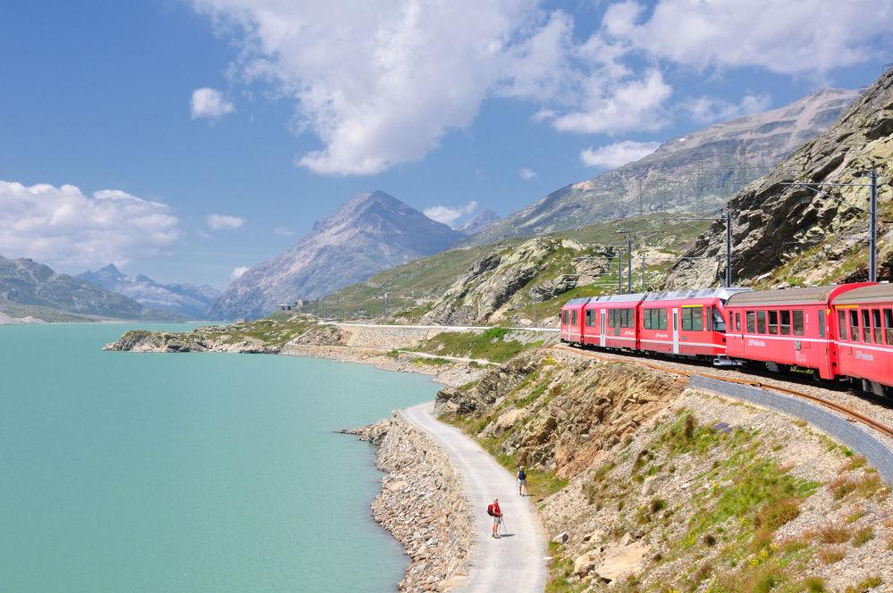 قطار يمر عبر بحيرة لاغو بيانكو في ممر بيرنينا في جبال الألب الإيطالية