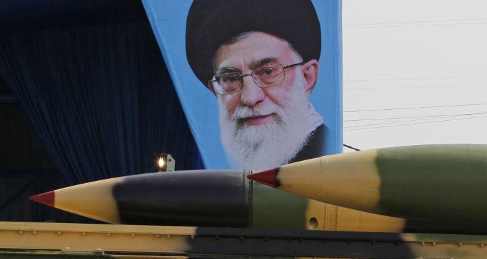 شاحنة عسكرية إيرانية تحمل صواريخ أرض جو أمام لوحة للزعيم الإيراني الأعلى آية الله علي خامنئي خلال استعراض بمناسبة عيد الجيش الإيراني السنوي في 18 أبريل/نيسان 2018 في طهران.
