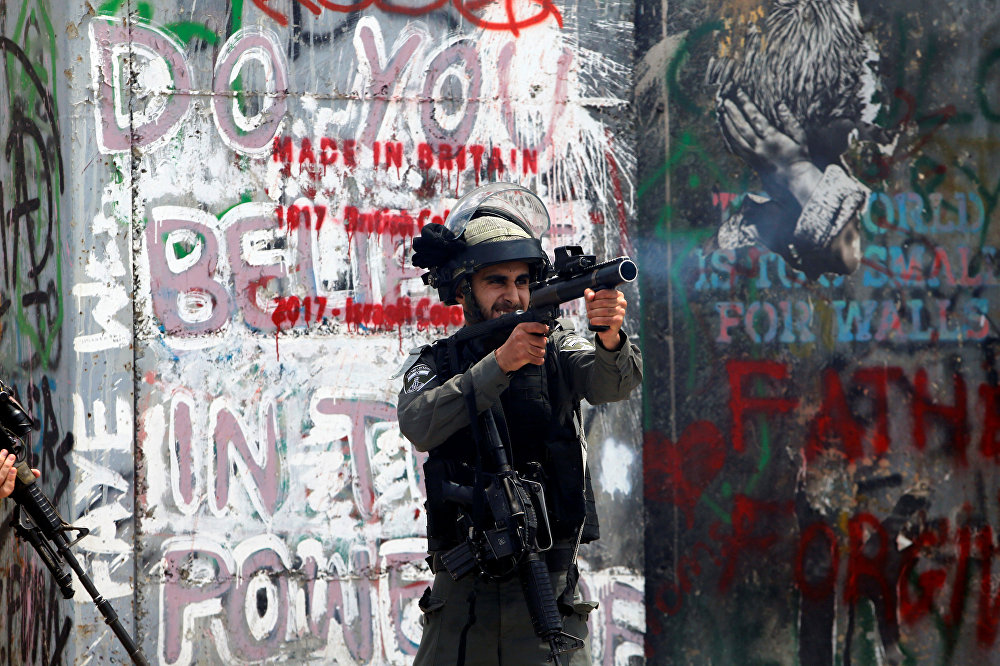 شرطي الحدود الإسرائيلي يطلق الغاز المسيل للدموع على المتظاهرين الفلسطينيين في بيت لحم خلال احتجاجات ضد نقل السفارة الأمريكية إلى القدس عشية الذكرى الـ 70 للنكبة، الضفة الغربية، فلسطين 14 مايو/ أيار 2018