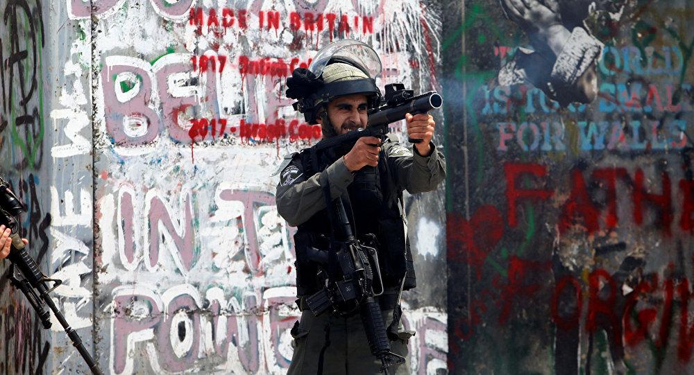 شرطي الحدود الإسرائيلي يطلق الغاز المسيل للدموع على المتظاهرين الفلسطينيين في بيت لحم خلال احتجاجات ضد نقل السفارة الأمريكية إلى القدس عشية الذكرى الـ 70 لـ النكبة، الضفة الغربية، فلسطين 14 مايو/ أيار 2018