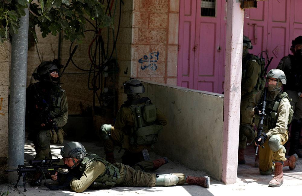 جنود إسرائليون يقنصون المتظاهرين الفلسطينيين عند حاجز قلنديا، جنوب رام الله، خلال احتجاجات ضد نقل السفارة الأمريكية إلى القدس عشية الذكرى الـ 70 للنكبة، الضفة الغربية، فلسطين 14 مايو/ أيار 2018