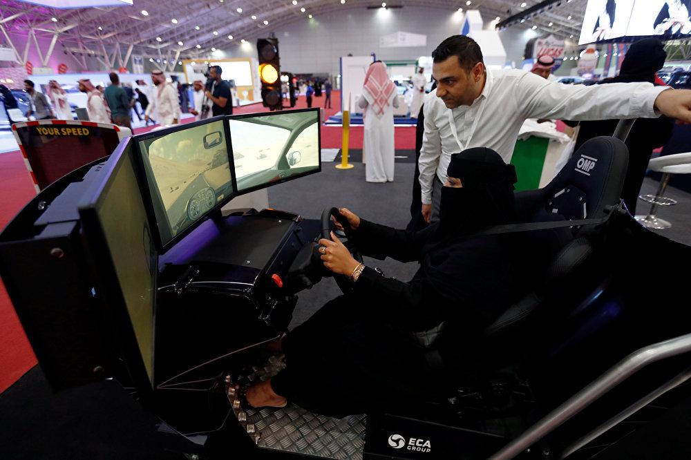 إمرأة تجلس على جهاز محاكاة في افتتاح المعرض النسائي الأول للسيارات، في المملكة العربية السعودية، 15 مايو/أيار 2018
