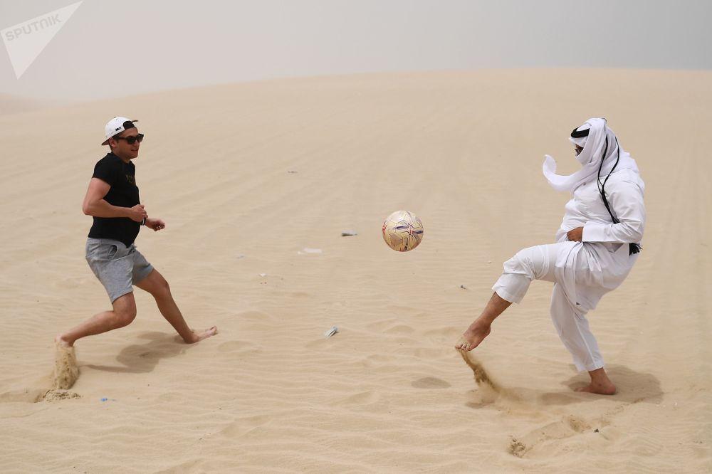رجال يلعبون كرة القدم في صحراء خور العديد، قطر