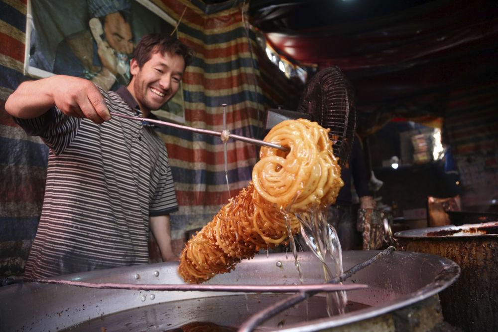 بائع الحلوى التقليدية قبل بدء شهر رمضان في كابول، أفغانستان 16مايو/ أيار 2018