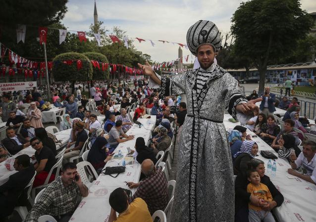 رجل يرتدي زي العهد العثماني في إفطار جماعي في أول أيام شهر رمضان المبارك في اسطنبول، تركيا 16 مايو/ أيار 2018
