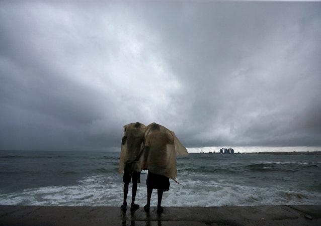 رجلان يحتميان من المطر أمام شاطئ البحر