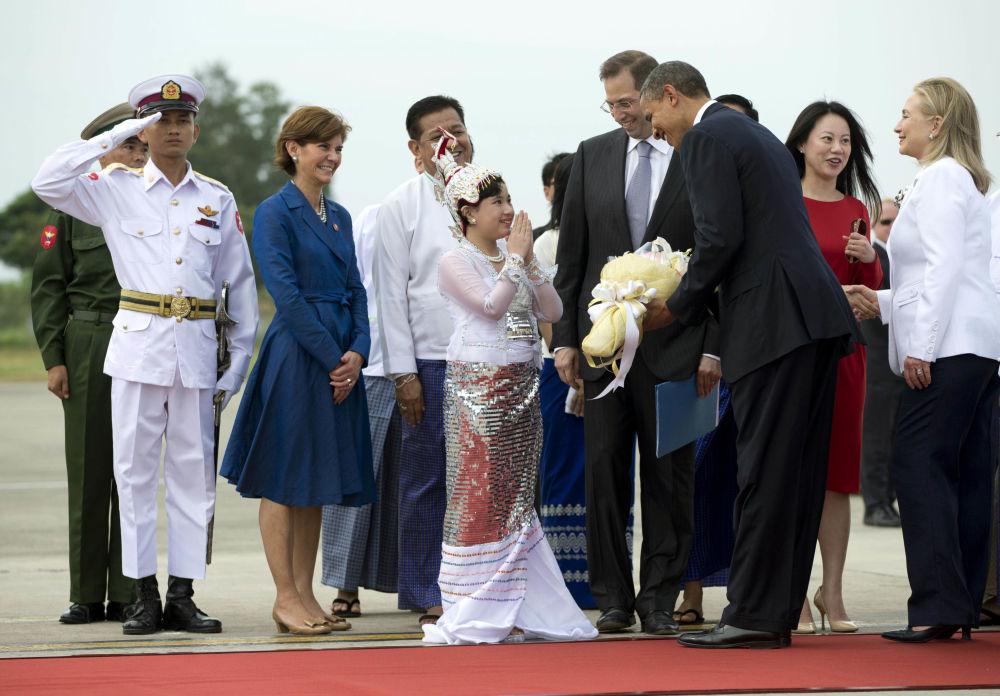 استقبال الرئيس الأمريكي باراك أوباما ووزيرة الخارجية الأمريكية هيلاري كلينتون بباقة من الأزهار لدى وصولهما إلى مطار يانغون الدولي في ميانمار، 19 نوفمبر/ تشرين الثاني 2012