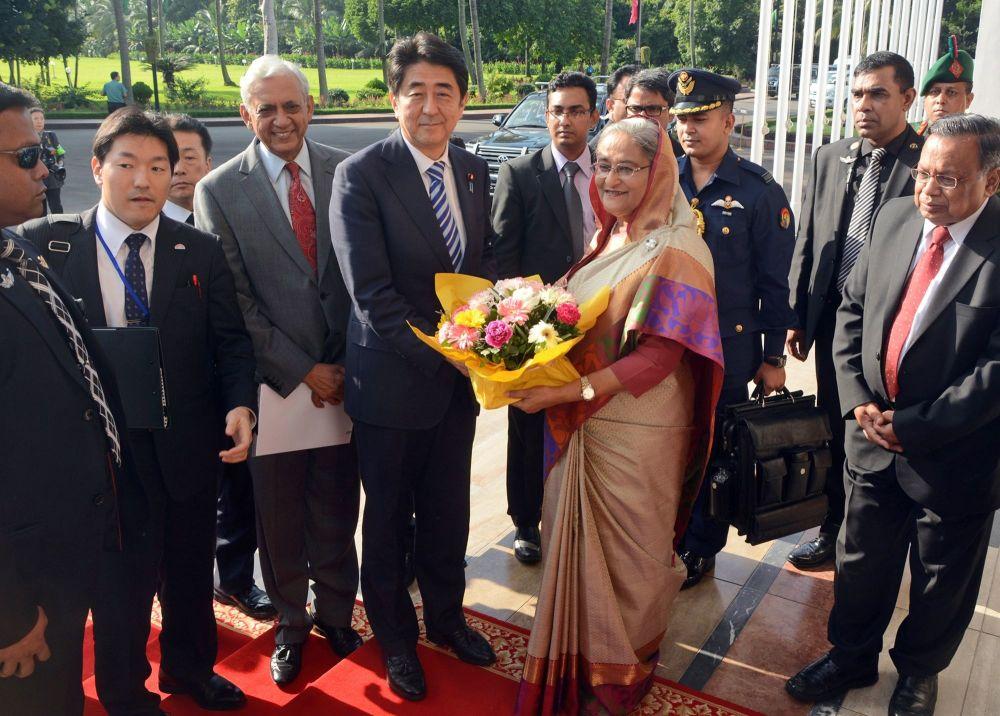 رئيس الوزراء الياباني شينزو آبي يهدي باقة من الأزهار لرئيسة بنغلاديش الشيخة حسينة قبل بدء الاجتماع في دكا، بنغلاديش  6 سبتمبر/ أيلول 2014