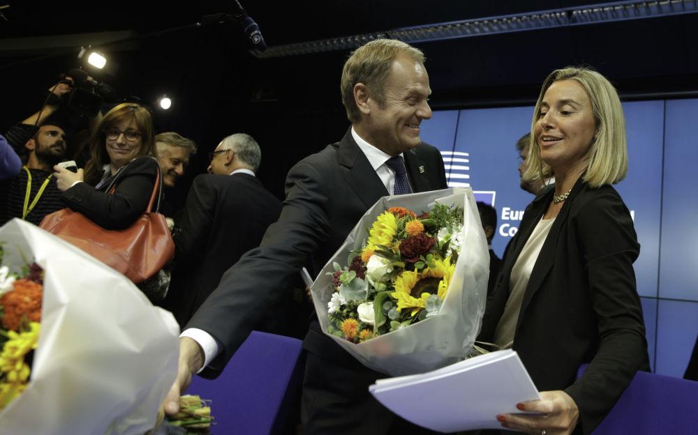 رئيس الوزراء البولندي دونالد توسك يهدي وزيرة الخارجية الإيطالية فيديريكا موغيريني  باقة من الزهور بعد مؤتمر صحفي في قمة الاتحاد الأوروبي في بروكسل، 30 أغسطس/ آب 2014