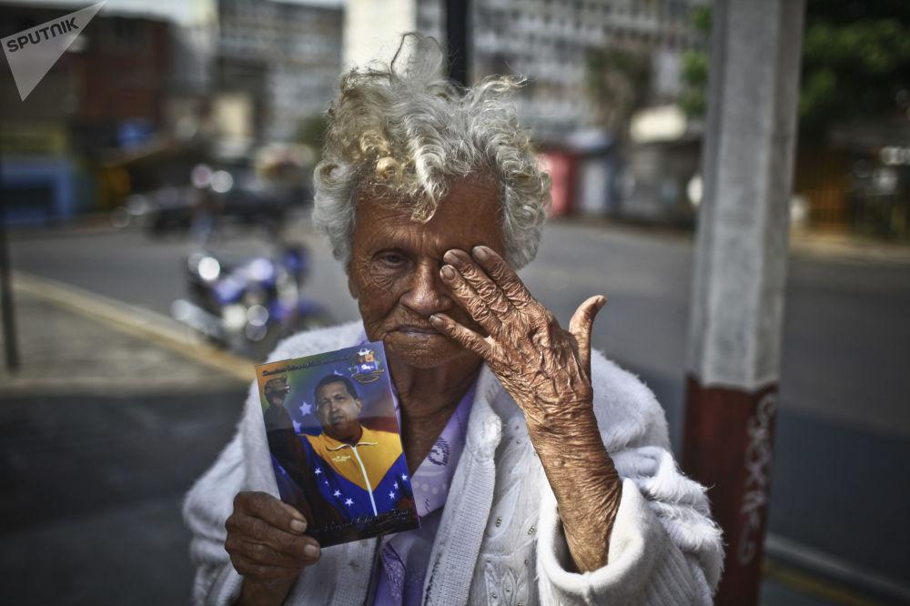 امرأة مسنة تحمل صورة الرئيس الفنزويلي الراحل هوغو تشافيز في كاراكاس
