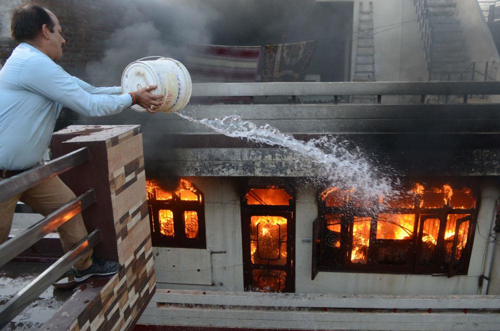 أحد السكان يحاول إخماد حريق في متجر كهربائي في أمريتسار، الهند في 20 مايو/ أيار 2018