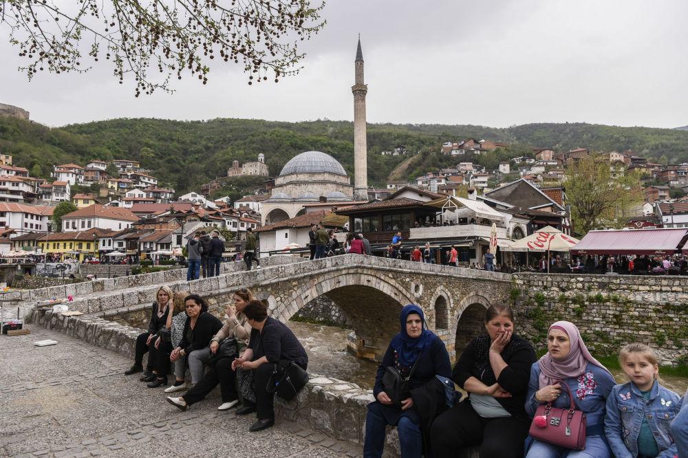الناس يجلسون بجانب جسر حجري يطل على مدينة بريزرين، كوسوفو