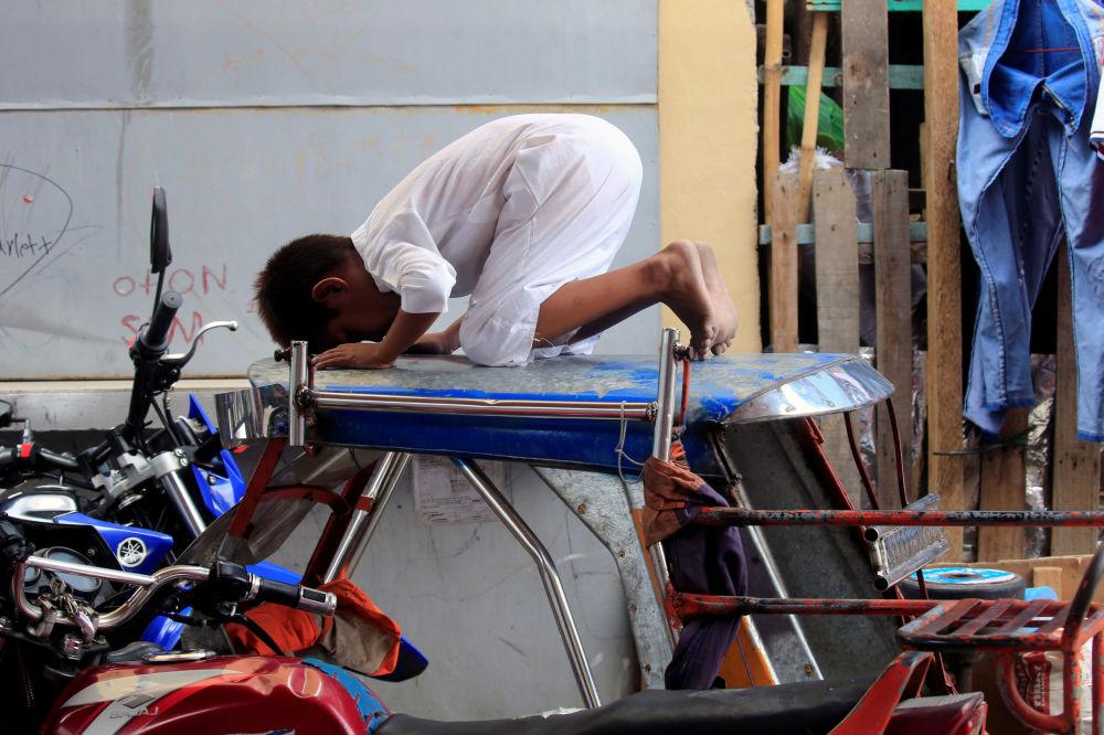 صبي فلبيني يصلي على سطح سيارة خارج مسجد في مدينة توندو، الفلبين 18 مايو/ أيار 2018