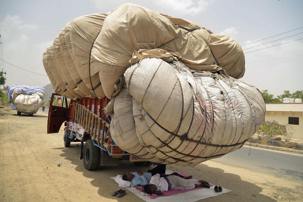 رجال هنديون ينامون في ظل حاوية من أكياس بداخلها قش المتدلية من الشاحنة لاستخدامها كعلف للحيوانات، في يوم صيفي حار في ولاية راجستان الغربية في 30 مايو/ أيار 2018