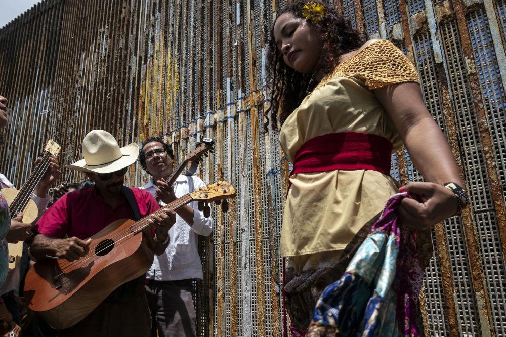 موسيقيون وراقصون في فعالية فاندانغو فرونتيريزو (Fandango Fronterizo) السنوية، في متنزه الصداقة على الحدود بين الولايات المتحدة والمكسيك في بلاياس دي تيخوانا، ولاية باجا كاليفورنيا، شمال غرب المكسيك، في 26 مايو/ أيار 2018