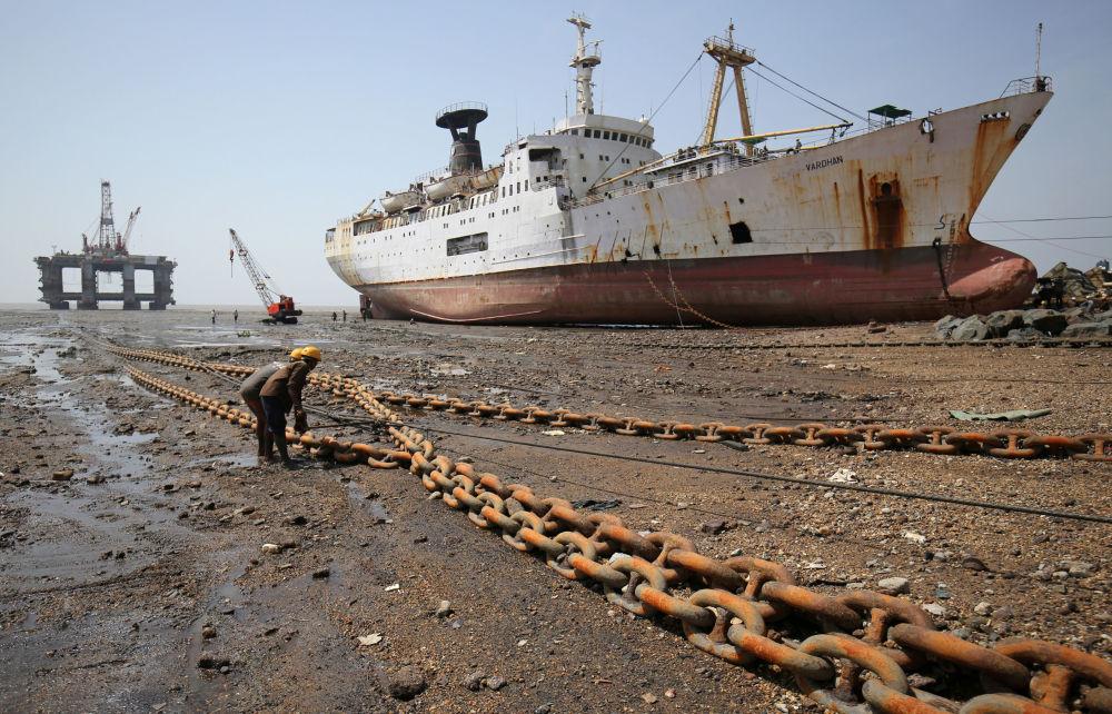 عمال يسحبون حبلا مرتبطا بحفارة نفطية لتفكيكها في حوض ألانغ لبناء السفن في ولاية غوجارات الغربية، الهند 29 مايو/ أيار 2018