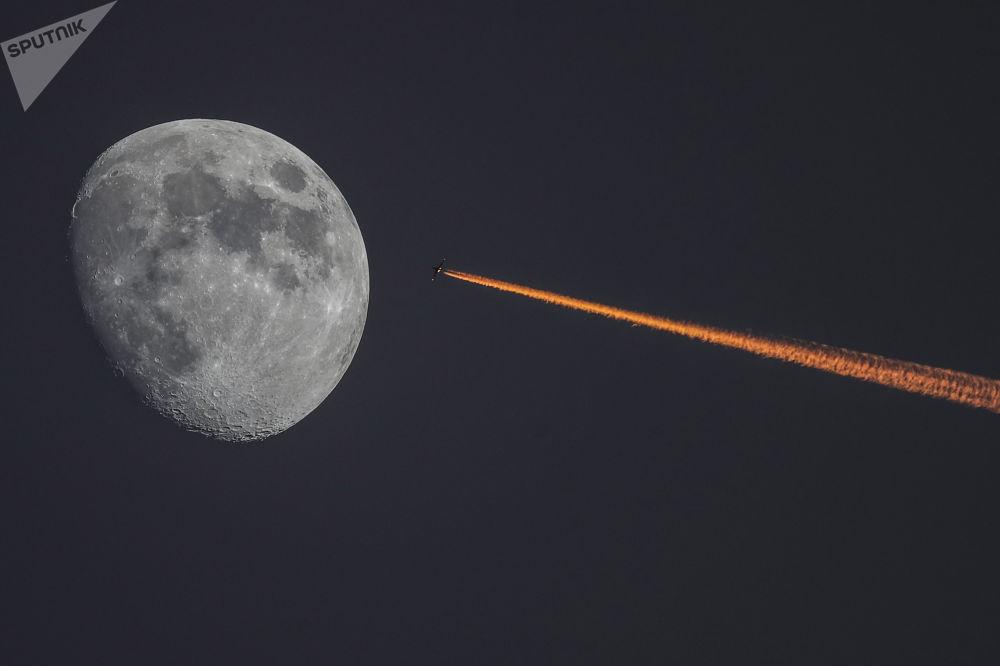 القمر وطائرة على خلفية غروب الشمس