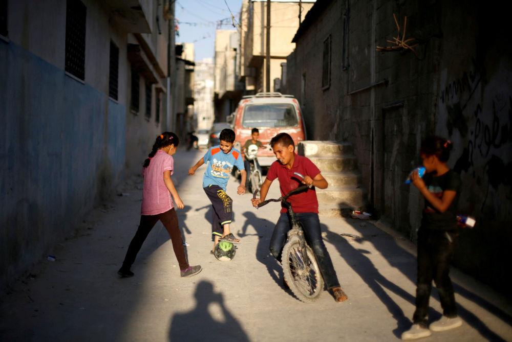 أطفال فلسطينيون يلعبون الكرة في أحد شوارع مخيم البقعة بالقرب من عمان، الأردن 29 مايو/ أيار 2018