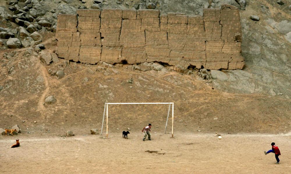 صبيان يلعبون كرة القدم في موقع أثري بوروتشوكو في ليما، 6 أغسطس/ آب 2008