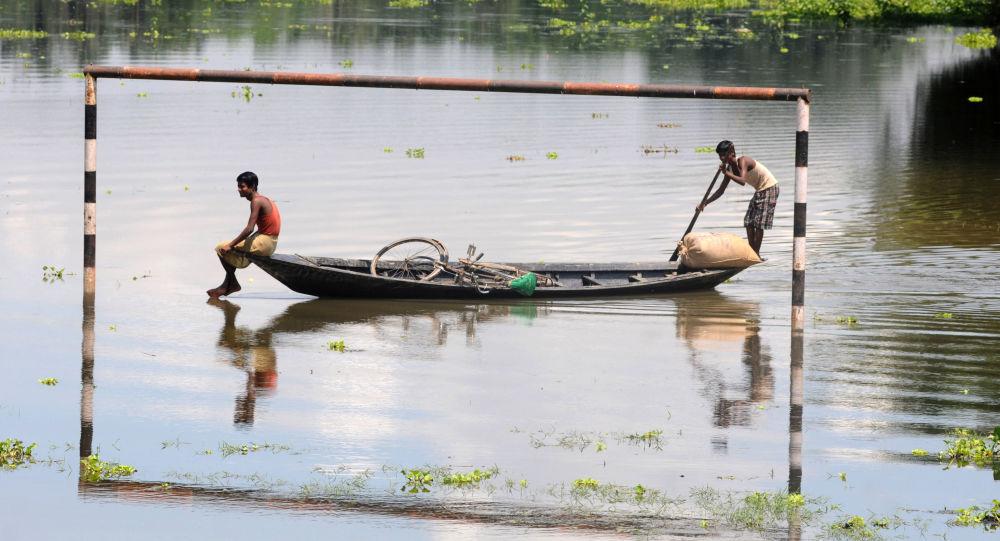 القرويون الهنود المتضررون من الفيضانات يمرون في مراكبهم بجوار مرمى مغممور جزئيا في قرية موكاتا، على بعد 70 كم من جواهاتي، الهند 11 يوليو/ تموز 2013