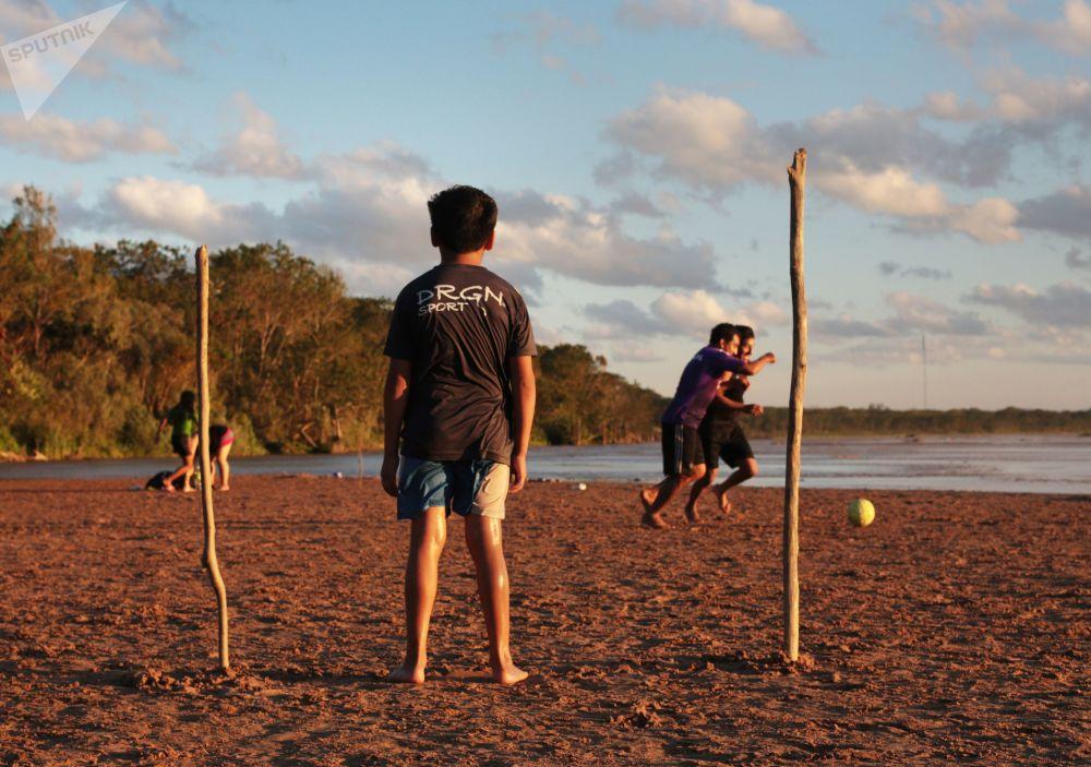 أطفال يلعبون كرة القدم بالقرب من نهر يبراي في مدينة سانتا كروز دي لا سييرا في بوليفيا