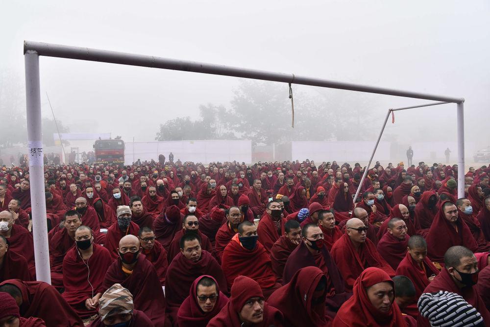 رهبان بوذيون يجلسون في ملعب لكرة القدم بجوار مرمى الأهداف بينما يستمعون إلى تعاليم الزعيم الروحي للتبت دلاي لاما في بودهغايا في الولاية الهندية بولاية بيهار في 5 يناير/ كانون الثاني 2018
