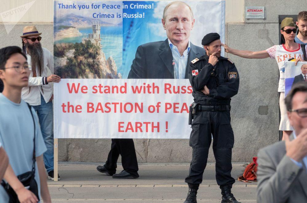 مواطنون من النمسا يحملون ملصقات تحمل صورة الرئيس الروسي فلاديمير بوتين مكتوب عليها شكرا للسلام في القرم! خلال اجتماعه مع الرئيس الاتحادي النمساوي ألكسندر فان دير بيلين في قصر هوفبورغ في فيينا