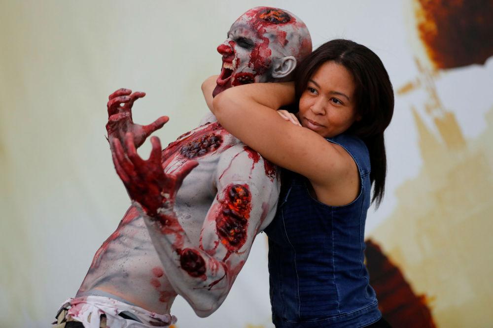 إحدى زوار معرض للألعاب تلتقط صورة مع زومبي في لوس أنجلوس، الولايات المتحدة الأمريكية 12 يونيو/ حزيران 2018