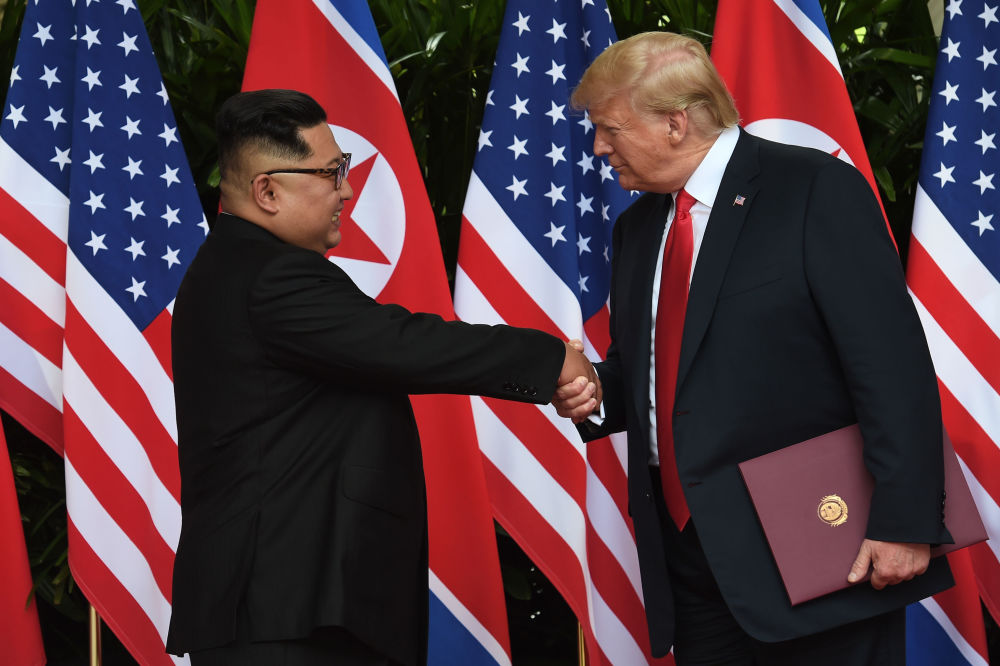 الرئيس الأمريكي دونالد ترامب والزعيم الكوري الشمالي كيم جونغ أون يتصافحان مع نهاية القمة التاريخية الأمريكية الكورية في سنغافورة، 12 يونيو/ حزيران 2018