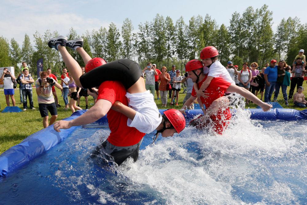 مهرجان بمناسبة عيد يوم روسيا يشاركون فيه الرجال بحمل زوجاتهن في كراسنويارسك، 10 يونيو/ حزيران 2018