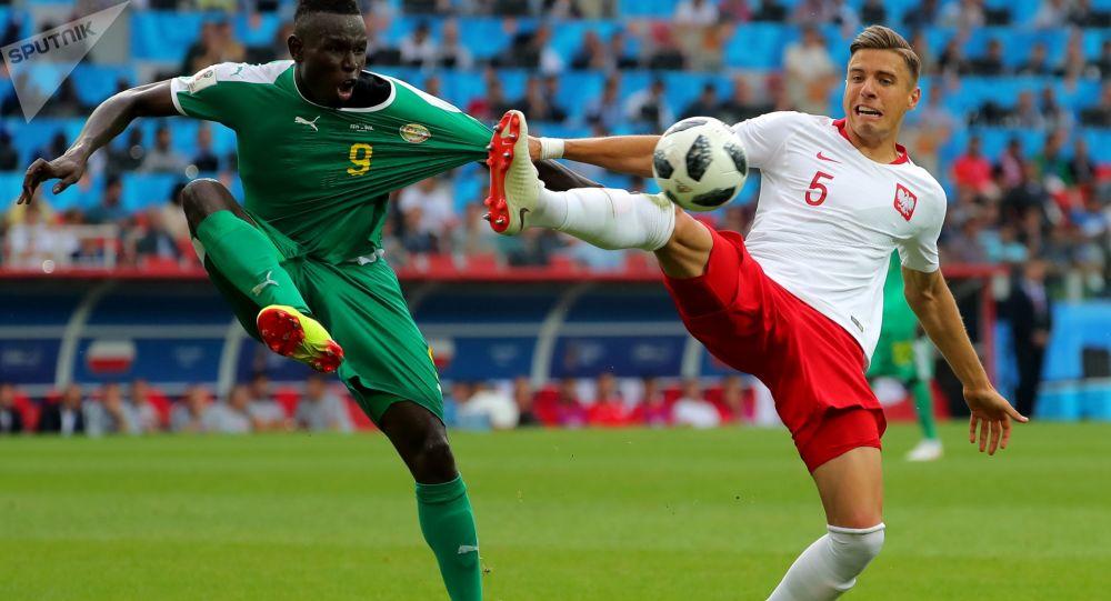 اللاعب السنغالي مامي بيرام ديوف واللاعب البولندي يان بيدناريك في المباراة التي جمعت فريقهما