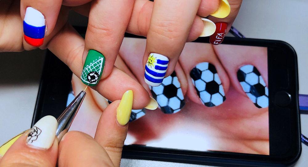 رسامة المناكير ترسم على اظافر فتاة أخرى أعلام المنتخبات، بمناسبة بطولة كأس العالم لكرة القدم 2018 في سامارا