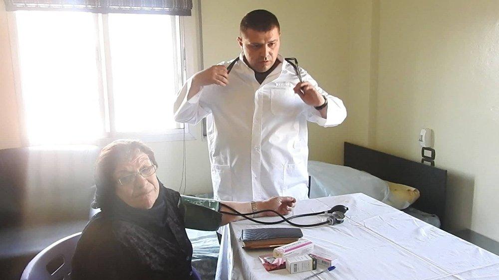 طبيب روسي يقوم بمعالجة مسنة سورية في ريف حماة - سوريا