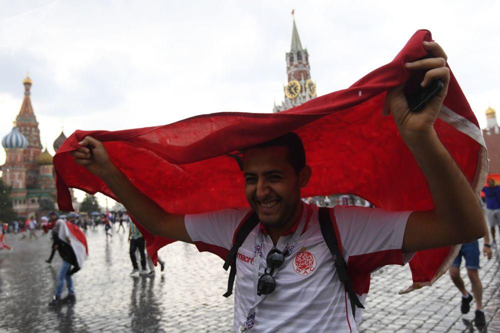 مشجع المنتخب المغربي يختبئ بالعلم من المطر على الساحة الحمراء في موسكو، 2018