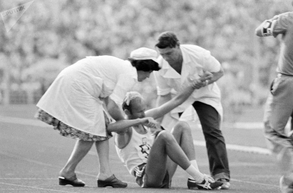 الأطباء الرياضيين يساعدون رياضيا مصابا على النهوض خلال  السابقات في دورة الألعاب الصيفية الـ 22 في موسكو، 1980