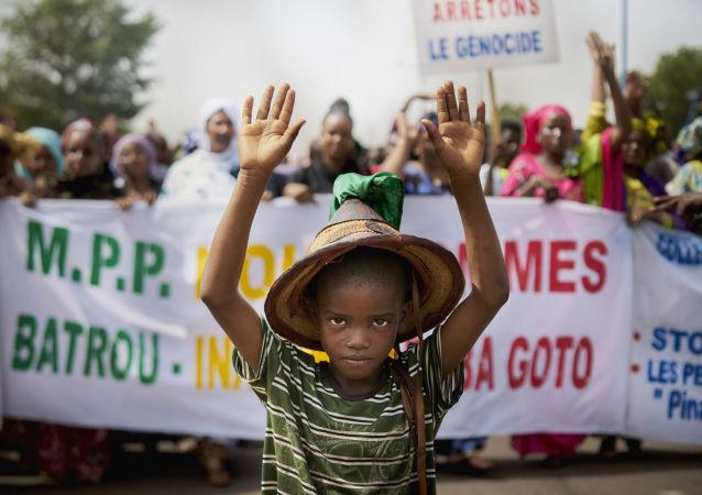 صبي من فولاني يقف أمام لافتة كتب عليها أوقفوا الإبادة الجماعية، خلال مسيرة صامتة نظمتها حركة من أجل السلام (Mouvement Peul et allies pour la paix)، وهي منظمة تضم شعبًا من أصل فولاني في مالي، كرد على المجزرة التي وقعت في كوماغا، في 30 يونيو/ حزيران 2018