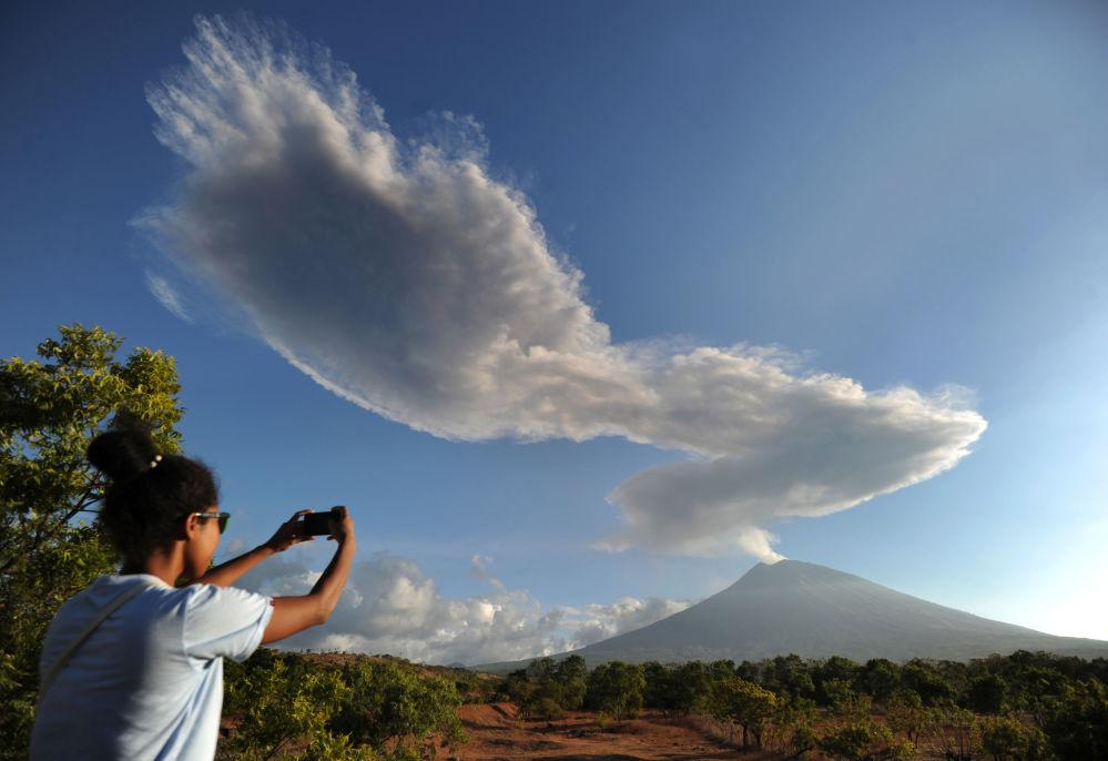 امرأة تلتقط صورة لبركان ماونت أغاونغ في جزيرة بالي، إندونيسيا 5 يوليو/ تموز 2018