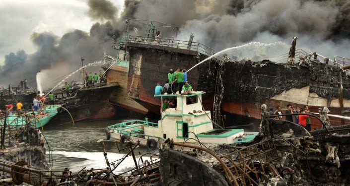 عمال إندونيسيون ورجال الإطفاء يخمدون حريق على قوارب الصيد في ميناء بينوا في دنباسار، في جزيرة بالي، إندونيسيا 9 يوليو/ تموز 2018