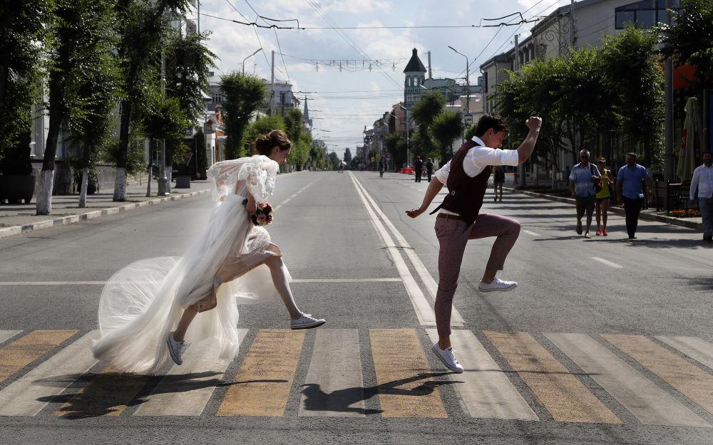 متزوجان جدد يعبران الطريق، خلال إقامة بطولة كأس العالم روسيا-2018 في مدينة سامارا، روسيا 8 يوليو/ تموز 2018