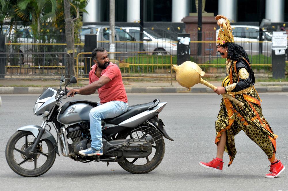 فنان يرتدي زي ياماراج (يمين الصورة)، وهو إله الموت الهندوسي، يركض خلف سائق يركب دراجة نارية بدون خوذة. وذلك في إطار حملة أسبوع السلامة على الطرق، التي نظمتها شرطة المرور في بنغالور في 10 يوليو/ تموز 2018.