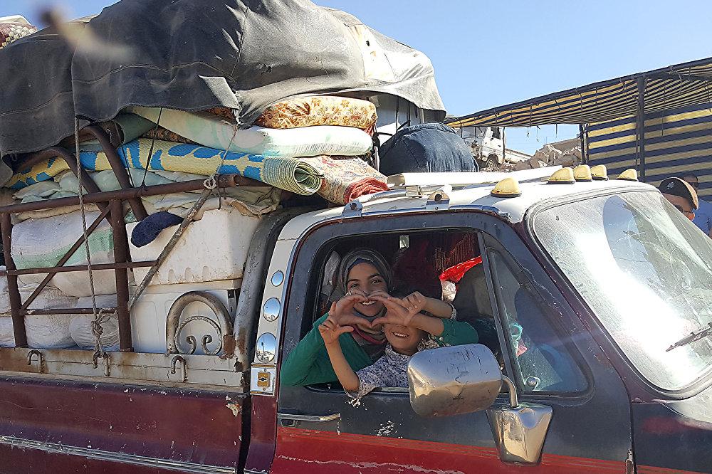 سوريون يغادرون مخيم  للاجئين بالقرب من مدينة عرسال اللبنانية