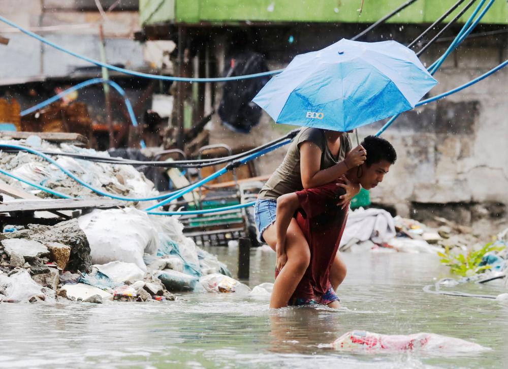رجل يحمل امرأة على ظهره لعبور شارع مغمور بالمياه بعد  هطول أمطار موسمية وعاصفة مدارية سون-تينه في مدينة كويزون، مترو مانيلا، في الفلبين 17 يوليو/ تموز 2018