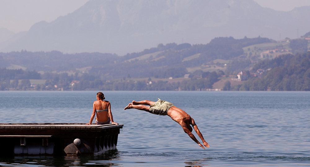 رجل يقفز الرجل في بحيرة زوغ في سويسرا هربا من حر الصيف