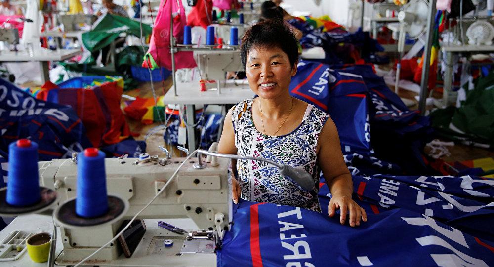 عاملة صينية في مصنع لتصنيع أعلام حملة إعادة انتخاب الرئيس الأمريكي دونالد ترامب في عام 2020