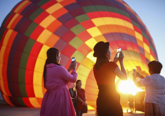 سياح يلتقطون صورا للمنطاد قبل انطلاقه  في رحلة في كابادوكيا، تركيا